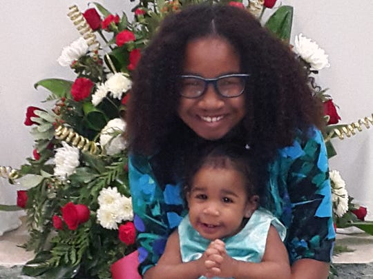 Ayana Pinkney, 12, says she's considering giving up meat and some technology this Lent. Pictured with her is her sister Avery Jane, 1.