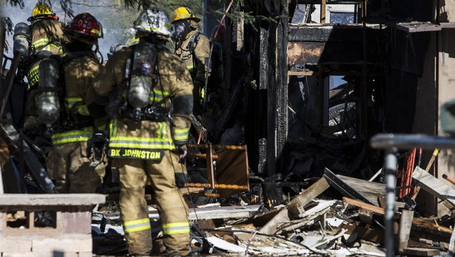 Firefighters work after an explosion killed one person and critically injured another at a house on Fillmore Street near Grand Avenue on Dec. 21, 2017, in Phoenix.