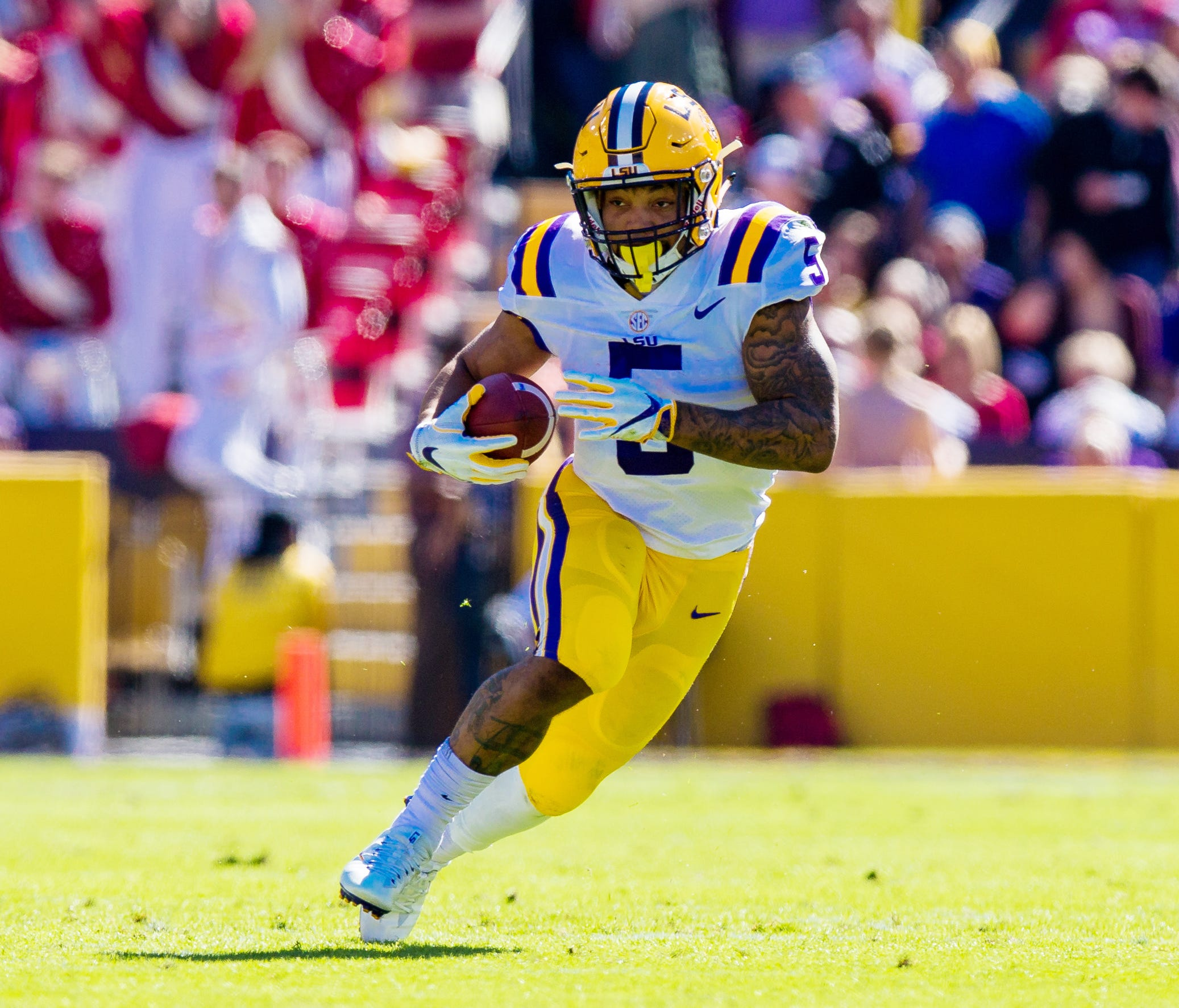 LSU Tigers running back Derrius Guice (5) runs against the Arkansas Razorbacks during the first half at Tiger Stadium.