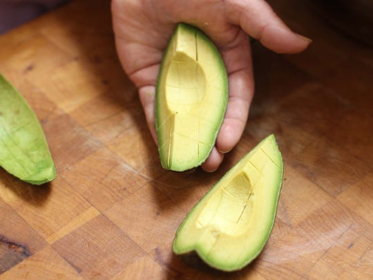 Cubing an avocado while it's still in the skin is a simple technique for a tossed salad.