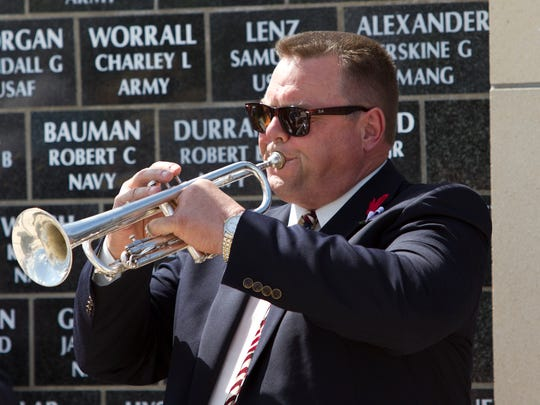 "Sen. Jon Tester plays ""Taps"" at the conclusion of the Memorial Day ceremony at the Montana Veterans Memorial on River Drive."