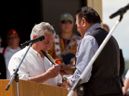 "Marvin Weatherwax, a professor at the Blackfeet Community College and veteran, presents Great Falls mayor Michael Winters with an eagle feather and a new name in the Blackfeet tradition as thanks for his role in making sure the Native American community, the Blackfeet in particular, were included among those honored at the Veterans Memorial. Mayor Winters' new name in Piegan translates to ""Brave Eagle."""
