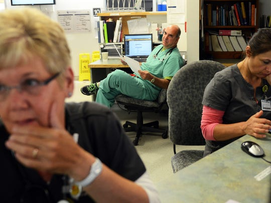 Dr. Steven Motarjeme, center, works with registered nurses Peggy Hatfield, left, and Ronda Robinson, in the Emergency Department at Park Ridge Health near Hendersonville Tuesday morning.