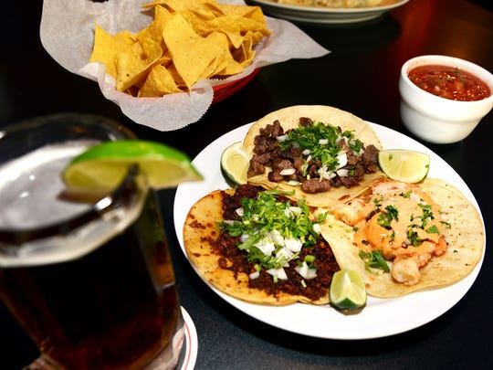 A plate of chorizo, shrimp and carne asado tacos with chips and salsa with a chilled mug of Dos Equis beer at Tacos Jalisco.