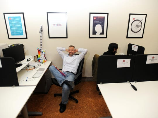Craig McAnsh is photographed in the offices of Mojo Coworking in 2014 at their offices at 60 Market St. Co-worker Shantanu Suman works at his station at right.
