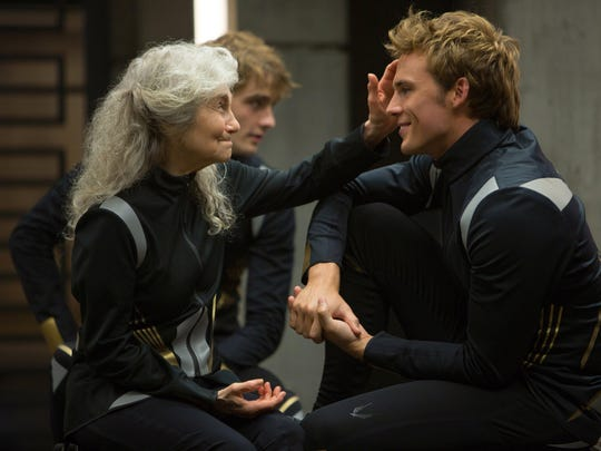 "Mags (Lynn Cohen) and Finnick Odair (Sam Claflin) play tributes who are teamed up in ""The Hunger Games: Catching Fire."""