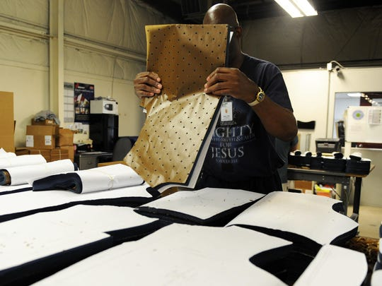 Using his sense of touch on wax paper, Walter Chambers assembles portions of garments being manufactured at Industries for the Blind in Asheville on Wednesday morning. The facility hosted representatives with the Textiles and Apparel Group or, TAG, this week.