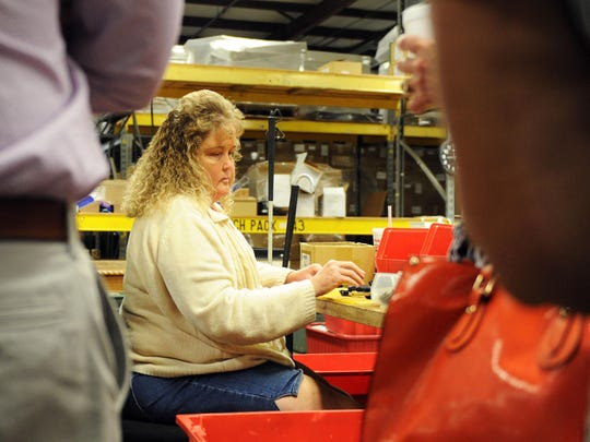 Kathy Hardwood is blind and uses her sense of touch to assemble portions of a new stapler being produced at Industries for the Blind in Asheville on Wednesday morning. Hardwood was the plant's Employee of the Year in 2014. The facility hosted representatives with the Textiles and Apparel Group or, TAG, this week.