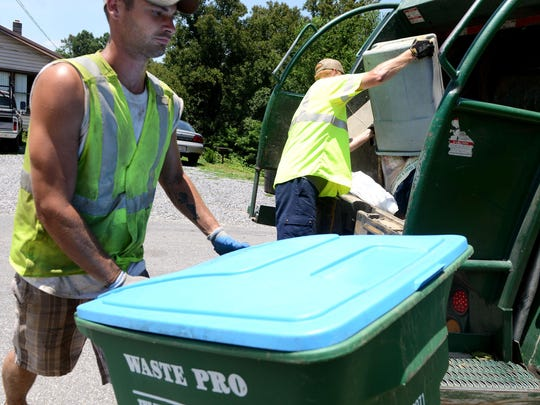 Caleb Smith,left, and Lewis Knight, of Waste Pro, load trash into a truck along Jordan Road in Swannanoa Wednesday afternoon.