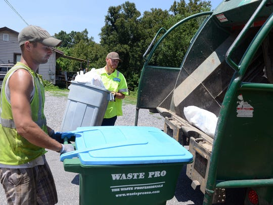 Caleb Smith, left, and Lewis Knight, of Waste Pro, load trash into a truck along Jordan Road in Swannanoa Wednesday afternoon.