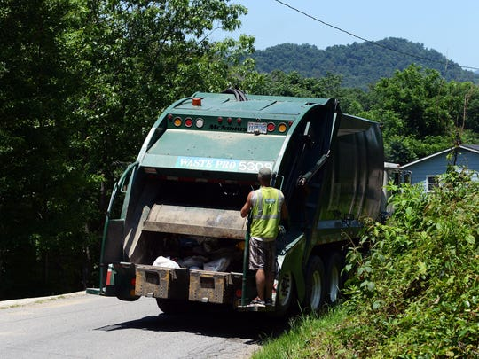 Caleb Smith, of Waste Pro, rides on the back of a trash truck along Jordan Road in Swannanoa Wednesday afternoon.