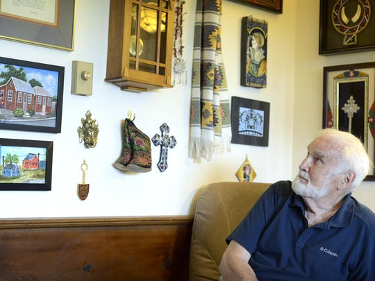 Dr. James Turpin looks at a wall of memorabilia from places he has visited around the world while working with the organization he founded, Project Concern International, at his home in Fairview.
