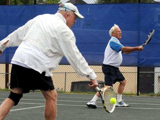 Ronald Keiger of Wilmington, and his partner Willis Anderson of Asheville warm up during doubles competition in the 75-and-older class during the annual City of Asheville Open tennis tournament at Aston Park.