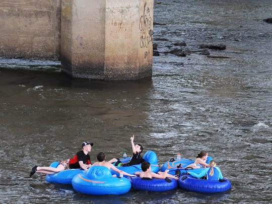 A group of tubers float past an outcropping of rocks in the French Broad River this past week.