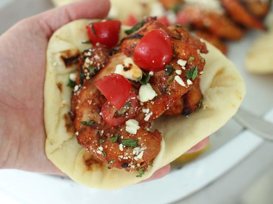Warm grilled gochujang chicken thighs with feta and fresh mint is wrapped in flatbread for serving.