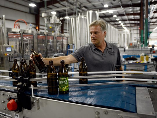 Rick Guthy, co-owner Wicked Weed inspects bottles in the brewery's massive production facility in Candler.