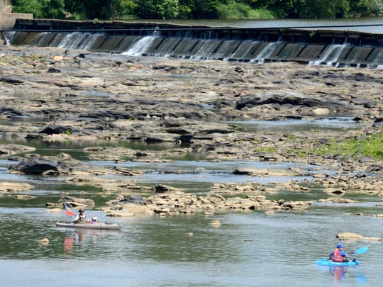 A trio of fisherman work the shallow pools near a dam in the French Broad River in downtown Marshall Tuesday.