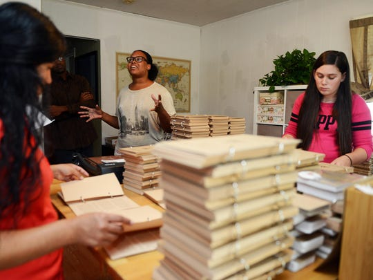 "Nicole Watkins, second from left, who started Journal Junky, creating homemade and handmade journals from recycled paper for sale speaks about the expansion of her business while employees Tatiana Argueta, left, and Janice Ender assemble copies of Benjamin Mathes's ""Thought Lozenges for Artists"" at her home in West Asheville."