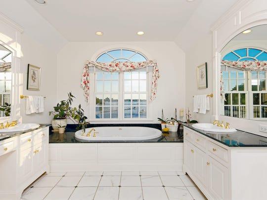The master bath has white marble flooring.