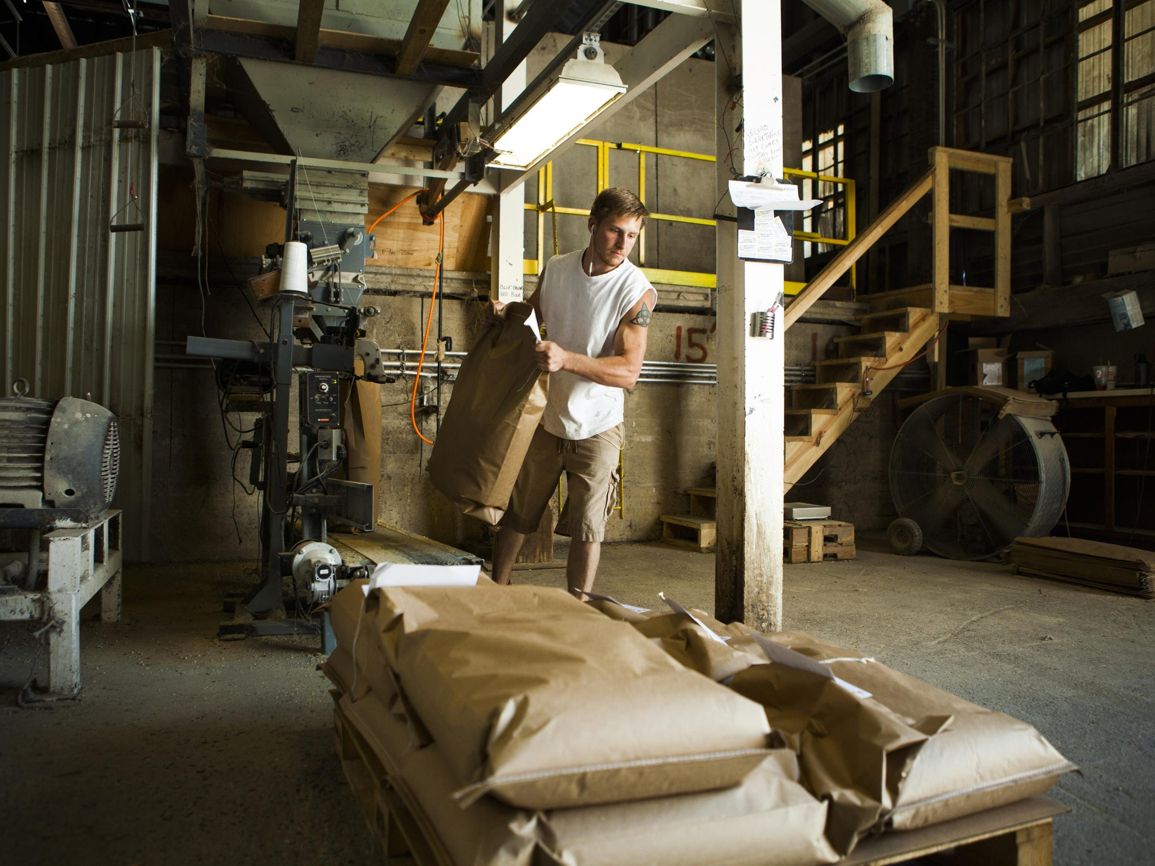 William Rochefort stacks feed bags underneath New Country Organics' mill in Waynesboro on Aug. 25, 2015.