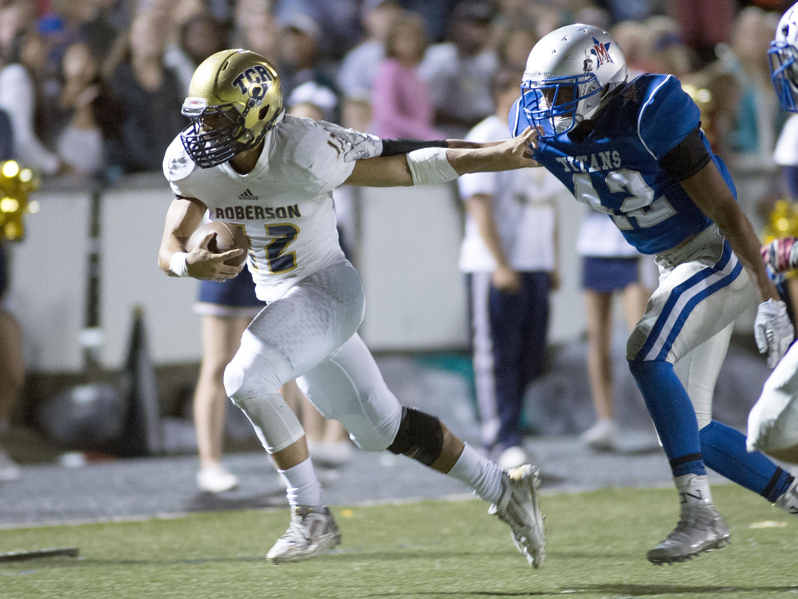 Roberson's Chris Barnwell, 12, uses a stiff arm before scoring for the Rams against McDowell.