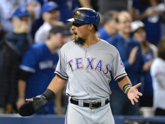 Texas Rangers' Rougned Odor gestures to his dugout after crossing home plate during the seventh inning in Game 5 of baseball's American League Division Series against the Toronto Blue Jays, Wednesday, Oct. 14, 2015 in Toronto. The Toronto Blues Jays beat the Texas Rangers 6-3. (Chris Young/The Canadian Press via AP) MANDATORY CREDIT