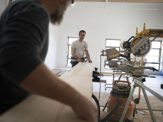 Contractors Jake Moran, left, feeds wood to a saw with Sean Reed in a building his team is renovating into apartments on Biltmore Avenue Wednesday Nov. 11, 2015.
