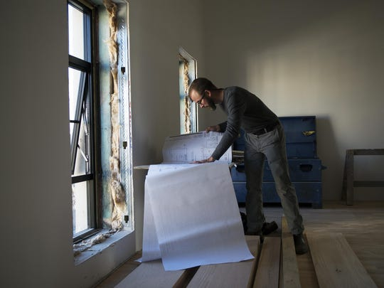 Contractor Sean Perry reviews blueprints in a building his team is renovating into apartments on Biltmore Avenue Wednesday Nov. 11, 2015.