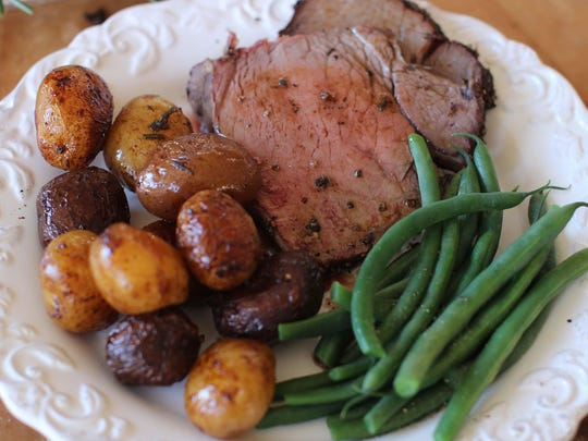 Add intense savory flavors from a rub of fresh rosemary and cracked peppercorns to your roast beef for a festive Christmas dinner.