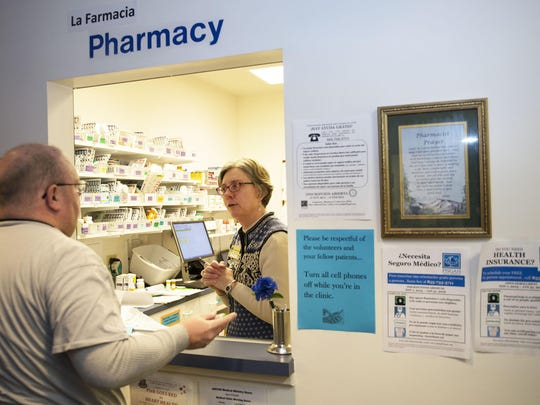 Pharmacist Laura Lever helps a man with his medication at Asheville-Buncombe Community Christian Ministries' free clinic south of downtown in this file photograph. Mission Health has partnered with ABCCM over the years to support the clinic.