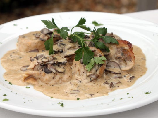 Chicken Farcito is is chicken breast stuffed with homemade sausage, broccoli rabe, mozzarella cheese and mushroom truffle sauce. It is served sliced.