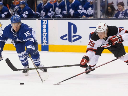 Toronto Maple Leafs' Nick Spaling (16) and New Jersey Devils' Seth Helgeson (39) reach for the puck during the second period of an NHL hockey game Thursday, Feb. 4, 2016, in Toronto. (Chris Young/The Canadian Press via AP)