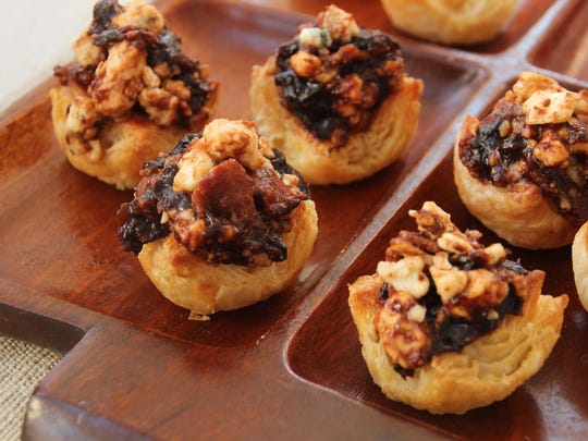 Puff pastry hors d'oeuvres filled with Gorgonzola cheese, chopped prunes and crumbled bacon.