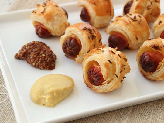 Puff pastry pig in a blanket topped with caraway seeds.