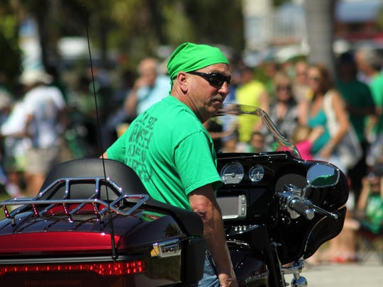 A biker, part of a fleet at the front of the parade, waits near the turn towards Veterans Community Park.