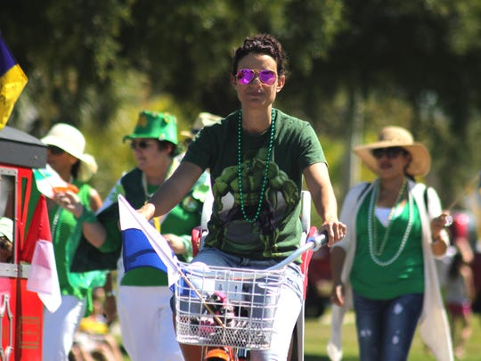 A cyclist forms part of one of the parade groups.