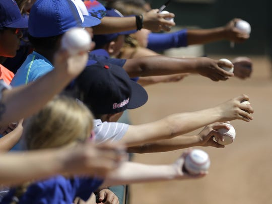 Baseball fans extend their arms for autographs before a spring training baseball game between the Los Angeles Dodgers and the Milwaukee Brewers Monday, March 14, 2016, in Phoenix. (AP Photo/Jae C. Hong)