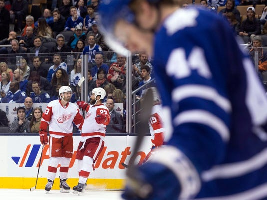 Detroit Red Wings' Kyle Quincey, center, celebrates with Pavel Datsyuk (13) after scoring the game winning goal as Toronto Maple Leafs' Morgan Rielly (44) reacts during third period NHL hockey action in Toronto on Saturday April 2, 2016. (Chris Young/The Canadian Press via AP)