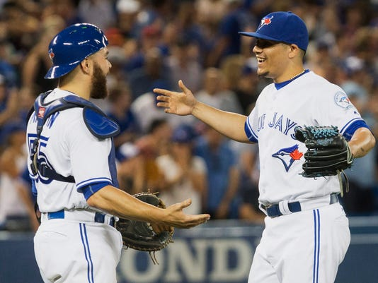 Toronto Blue Jays relief pitcher Roberto Osuna, right, celebrates with catcher Russell Martin after closing the ninth inning and sealing their 4-2 win over the San Diego Padres in baseball action in Toronto on Monday, July 25, 2016. (Chris Young/The Canadian Press via AP)