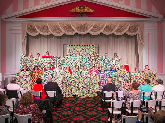 "Guests at last year's Grand Hotel Annual Spring Needle Art Seminar show off their ""Grand Illusion"" quilt, designed by Bonnie Hunter."