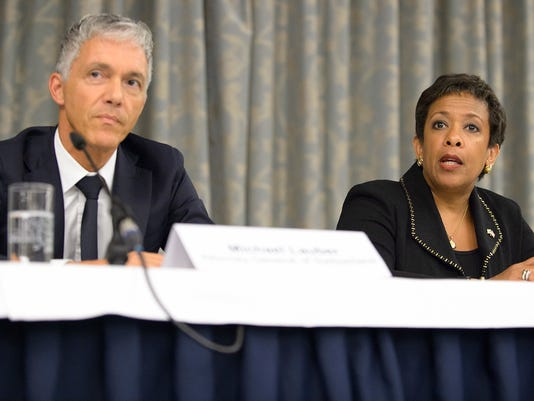 FILE - This is a Monday, Sept. 14, 2015 file photo of  Switzerland's Attorney General Michael Lauber,  left, US Attorney General  and Loretta Lynch, attend a news conference on soccer related criminal proceedings, in Zurich, Switzerland. FIFA has sent 1,300 pages of internal investigation reports into suspected bribery and corruption implicating world soccer leaders to Switzerland's attorney general. However, FIFA said Friday March 31, 2017 it was legally barred from publishing the full reports or commenting on the evidence or conclusions. ( (Anthony Anex/Keystone, File via AP)