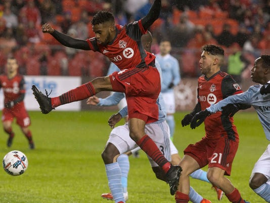 Toronto FC's Raheem Edwards, top, gets a shot off against  Sporting Kansas City during the second half of an MLS game in Toronto on Friday, March 31, 2017. (Chris Young/The Canadian Press via AP)