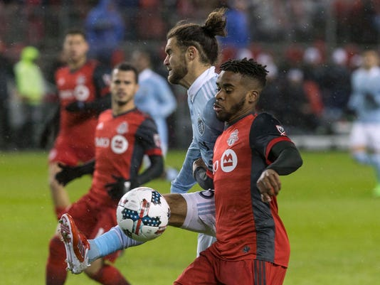 Sporting Kansas City's Graham Zusi, center, clears the ball from Toronto FC's Raheem Edwards during the second half of an MLS game in Toronto on Friday, March 31, 2017. (Chris Young/The Canadian Press via AP)