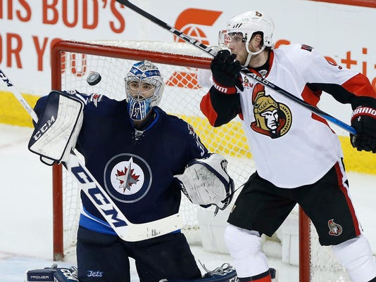 Winnipeg Jets goalie Connor Hellebuyck (37) gets to a high puck before Ottawa Senators' Bobby Ryan (9) can knock it down during third-period NHL hockey game action in Winnipeg, Manitoba, Saturday, April 1, 2017. (John Woods/The Canadian Press via AP)