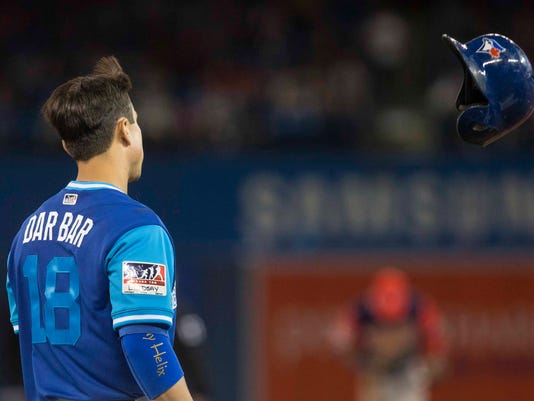 Toronto Blue Jays' Darwin Barney tosses his helmet after lining out against the Minnesota Twins during the fourth inning of a baseball game Friday, Aug. 25, 2017, in Toronto. (Chris Young/The Canadian Press via AP)