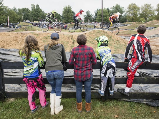Fans and BMX racers gather around a fenceline in Tom Sawyer State Park.