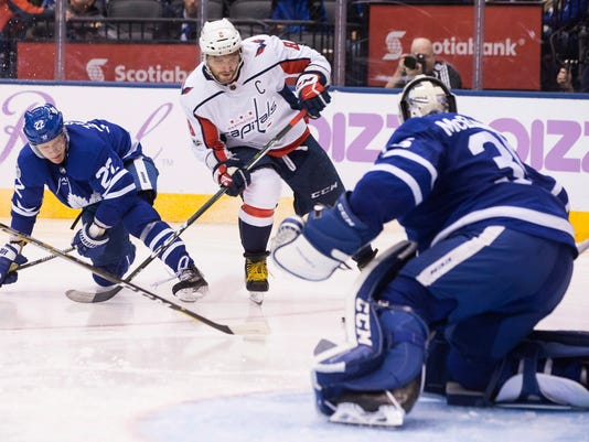 Washington Capitals left wing Alex Ovechkin, center, bears down on Toronto Maple Leafs goalie Curtis McElhinney as Leafs defenseman Nikita Zaitsev tries to defend during the third period of an NHL hockey game in Toronto on Saturday, Nov. 25, 2017. (Chris Young/The Canadian Press via AP)