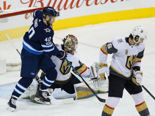 Winnipeg Jets' Tyler Myers' (not shown) shot goes through the legs of Las Vegas Golden Knights goalie Maxime Lagace, center, as Golden Knights' Colin Miller (6) defends and Jets' Joel Armia (40) looks on during first-period NHL hockey game action in Winnipeg, Manitoba, Friday, Dec. 1, 2017. (John Woods/The Canadian Press via AP)