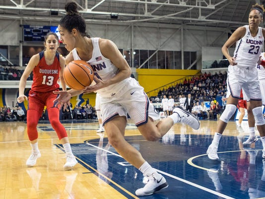 Connecticut guard Kia Nurse, center, looks for the pass as Duquesne's Julijana Vojinovic, left, looks on during first-half NCAA college basketball game action in Toronto, Friday, Dec. 22, 2017. (Chris Young/The Canadian Press via AP)