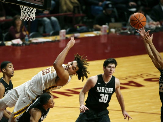 Minnesota center Reggie Lynch (22) flips over the back of Harvard guard Justin Bassey (20) as he goes up for a rebound in the first half of an NCAA college basketball game Saturday, Dec. 30, 2017, in Minneapolis. (Anthony Souffle/Star Tribune via AP)